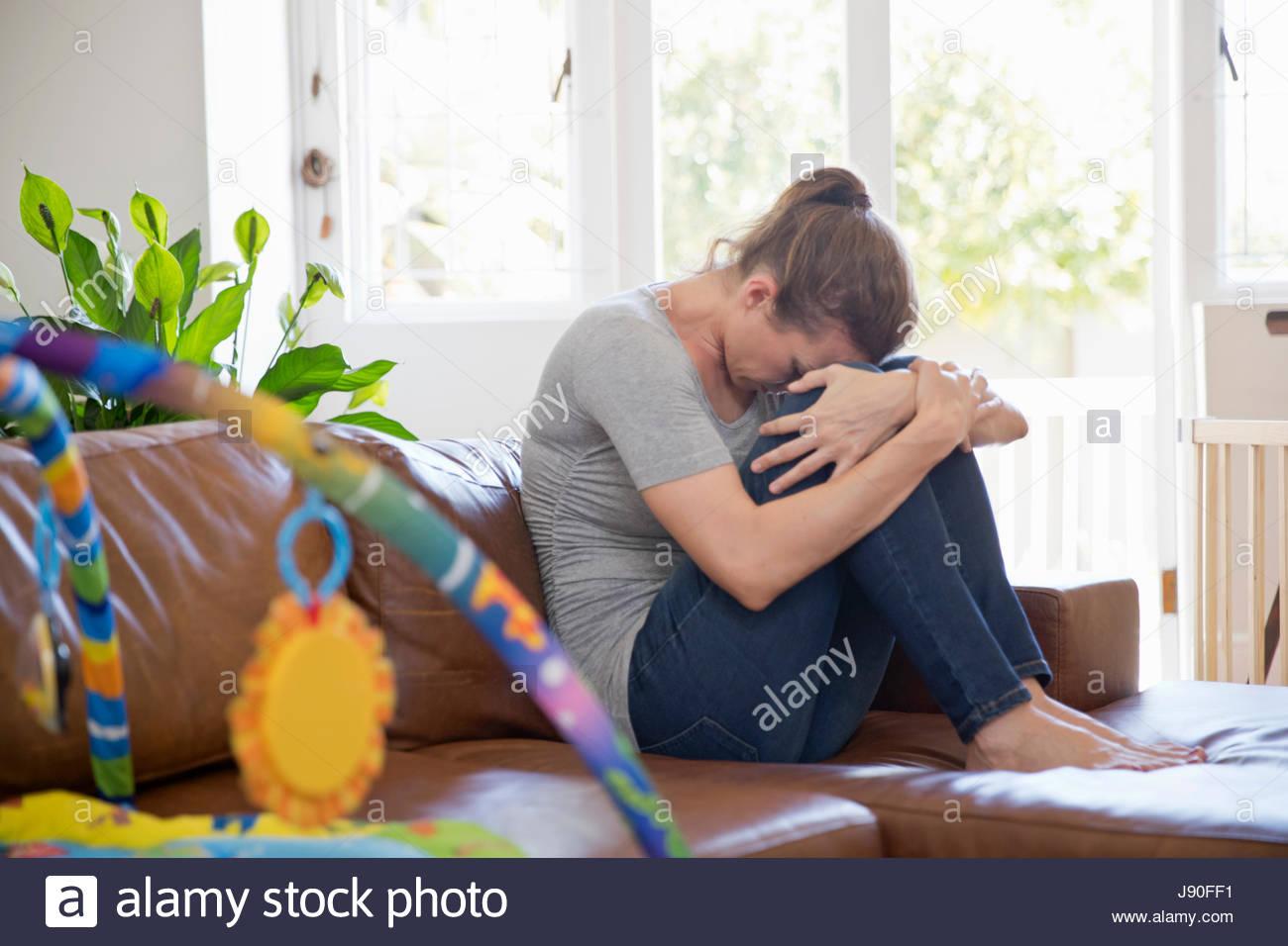 Madre infelice la sofferenza con Post Natal depressione si siede sul divano Immagini Stock
