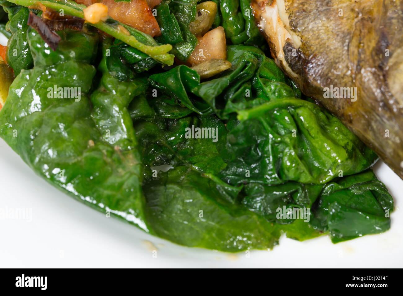 Warm insalata di spinaci con porri come guarnizione per cotto dorado. Macro. Foto può essere usato come un intero sfondo. Foto Stock