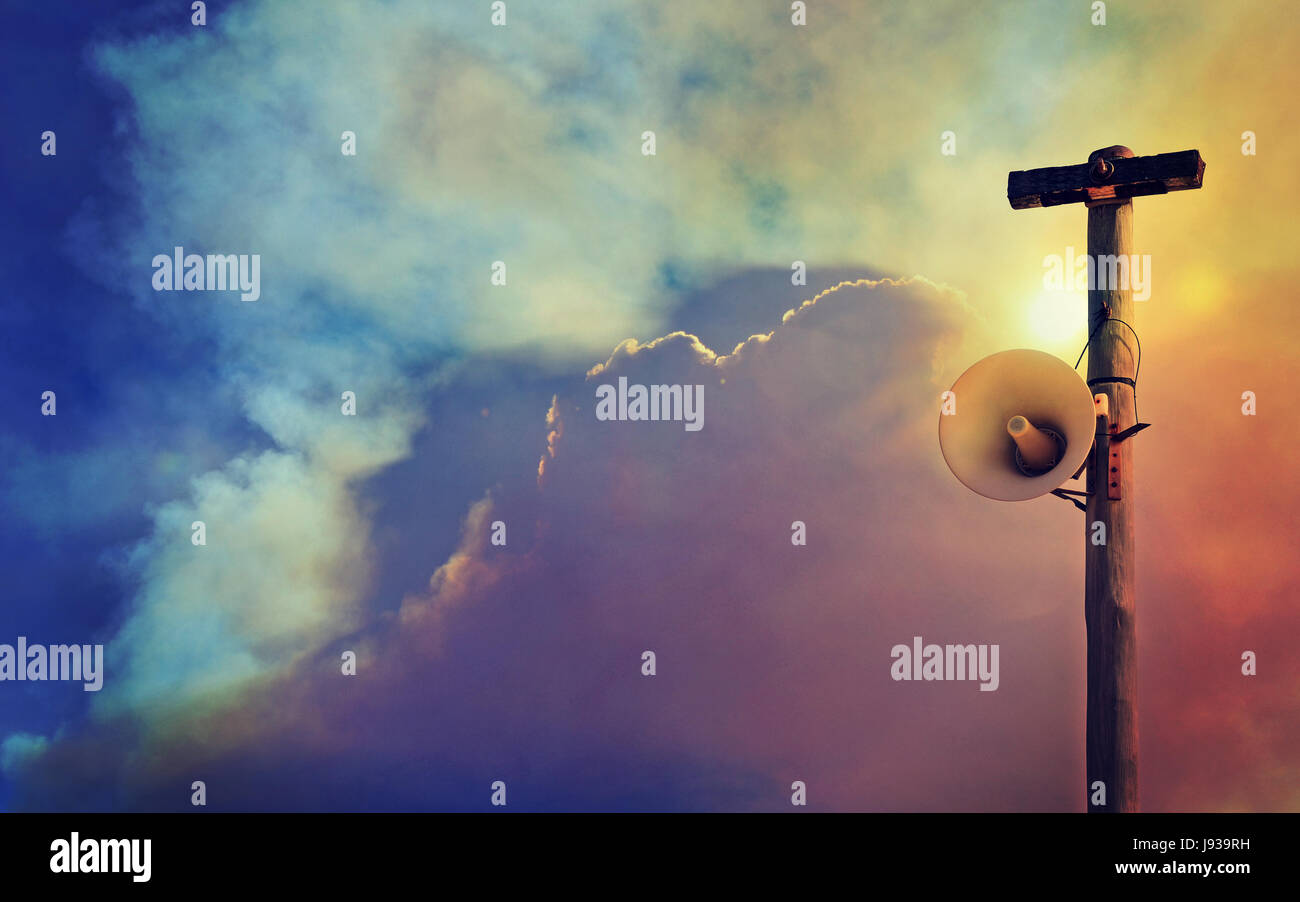 Altoparlante esterno sistema di avvertimento sul palo del telegrafo contro una piena di fumo sullo sfondo del cielo. Immagini Stock