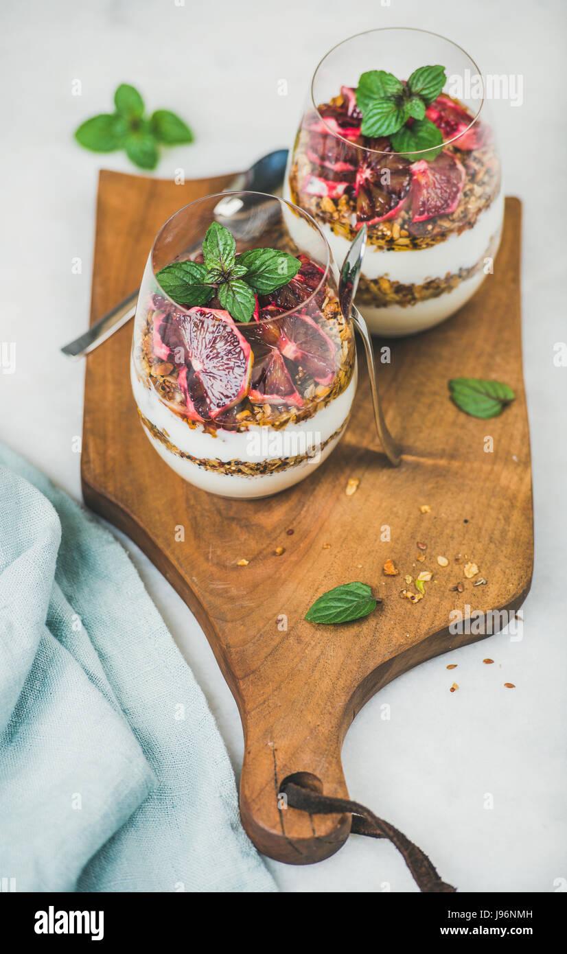 Sana colazione occhiali con yogurt e granola sul pannello di legno Immagini Stock