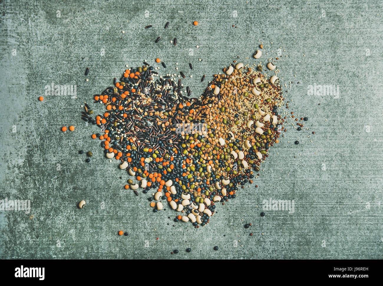 Vari cereali grezzi, fagioli e cereali in forma di cuore Immagini Stock