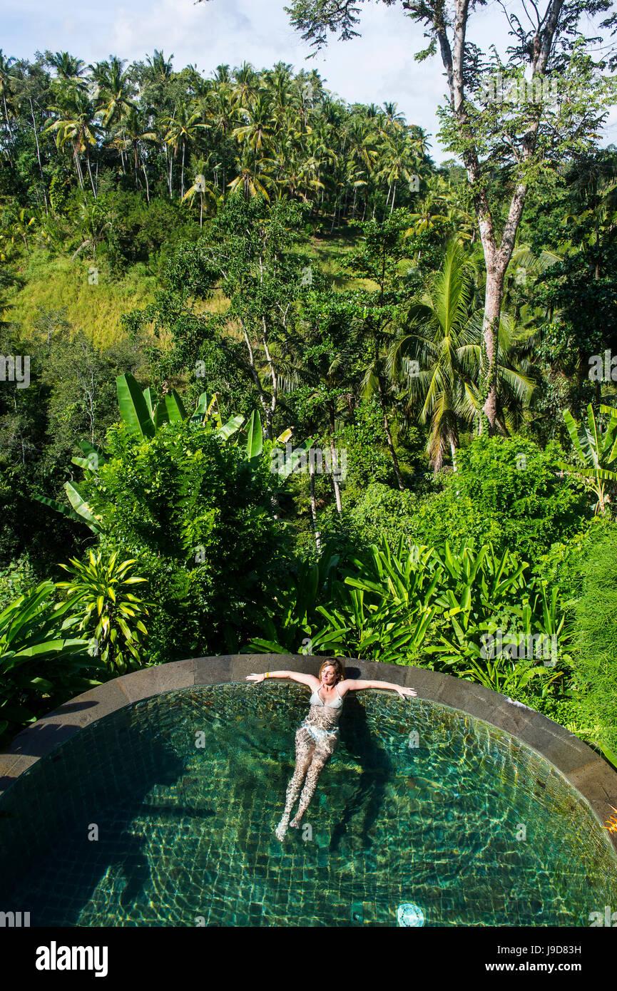 Donna godendo di un traboccare piscina al di sopra di una valle nel Kamandalu Resort Ubud, Ubud, Bali, Indonesia, Immagini Stock
