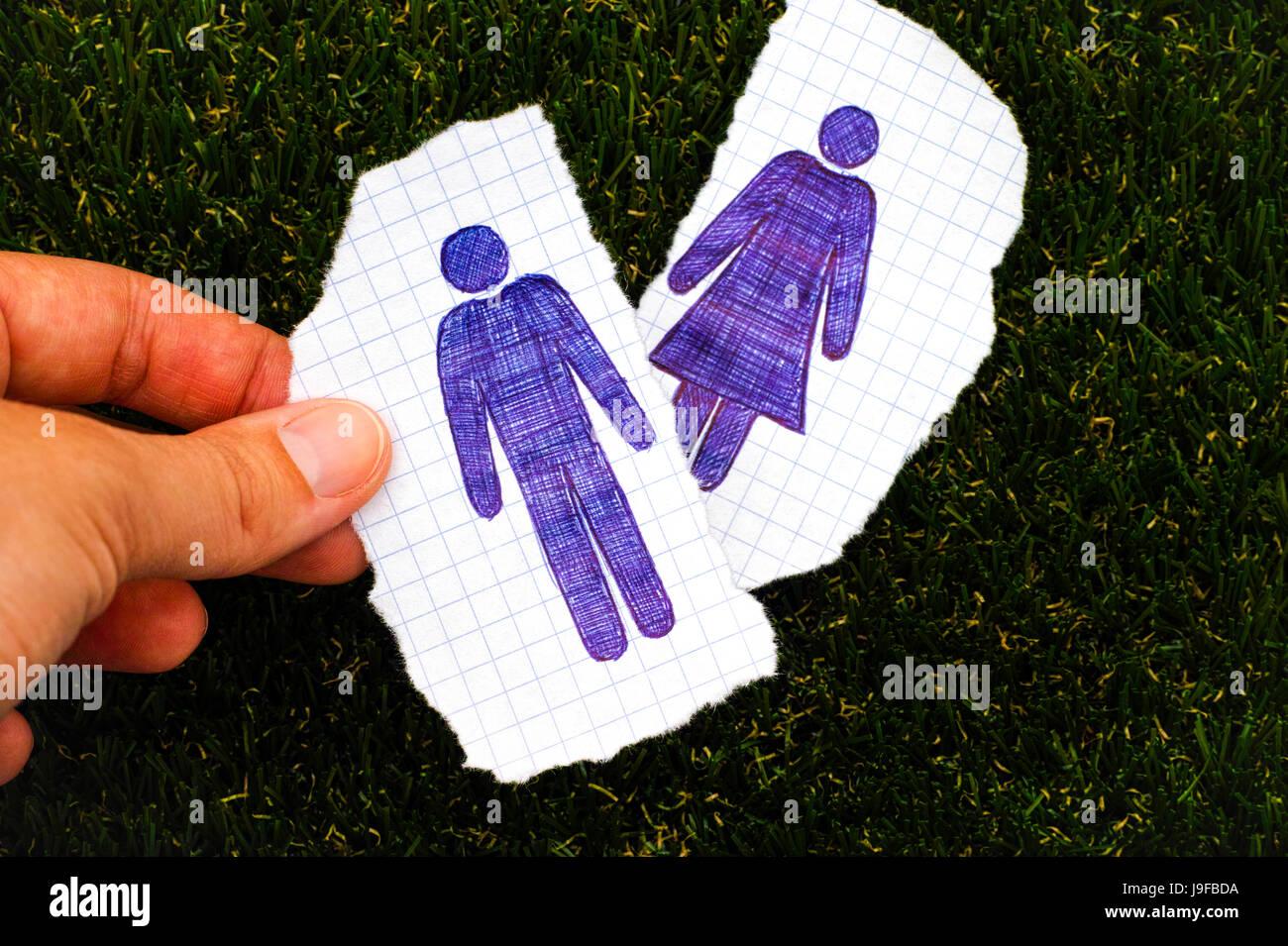 Persona dita tenendo pezzo di carta con disegnati a mano uomo figura. Altro pezzo di carta con disegnata la donna Immagini Stock