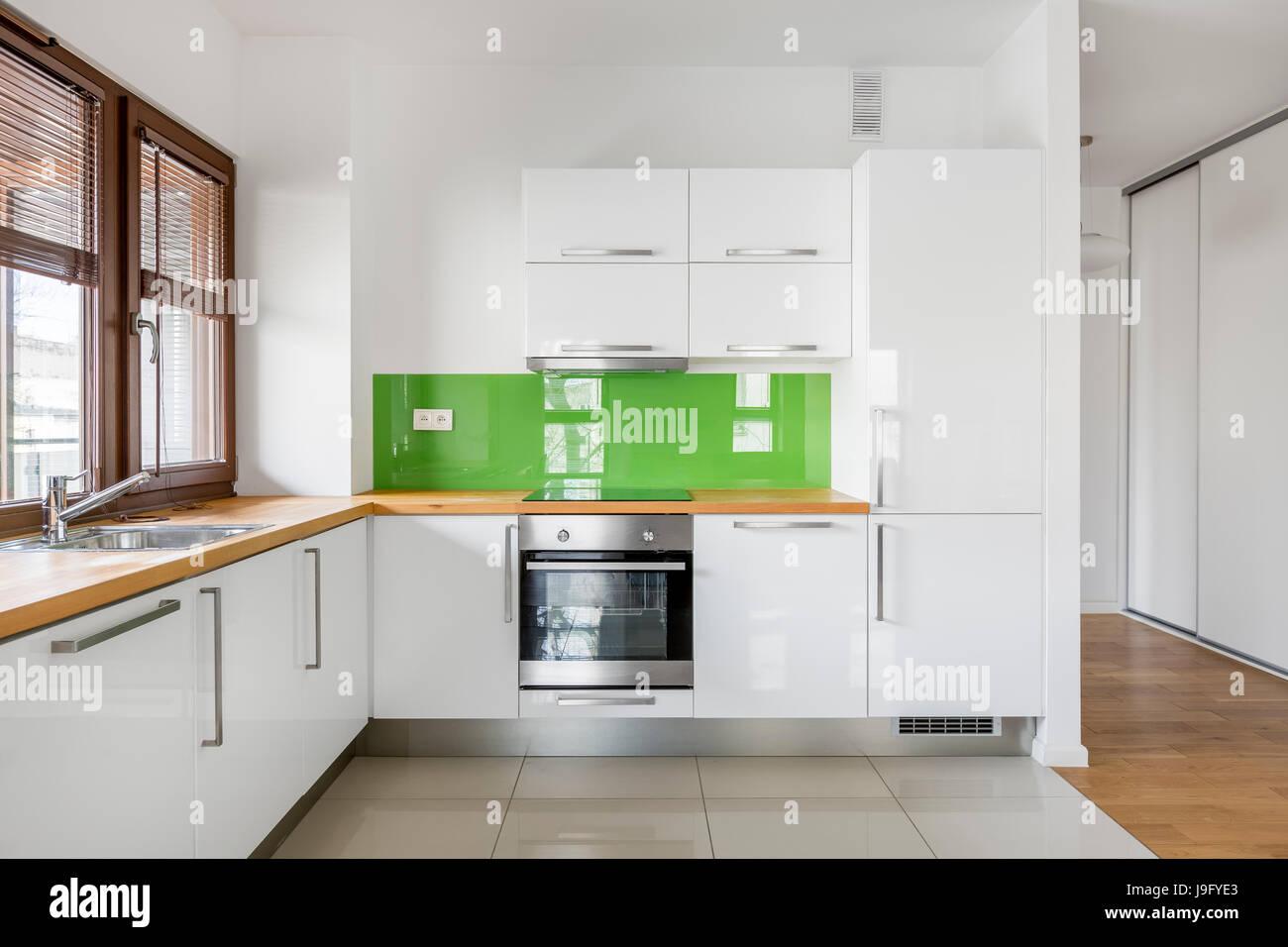 Elevata lucentezza, cucina bianca con una grande finestra, bancone ...