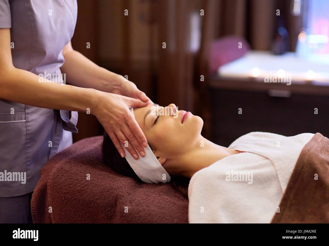 Donna con massaggio viso e testa a spa Immagini Stock