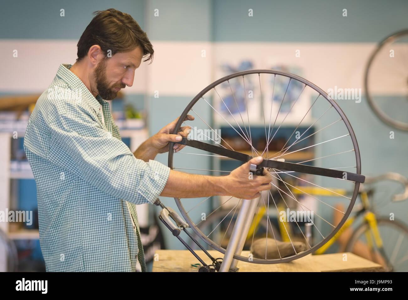Vista laterale del lavoratore focalizzato la riparazione della ruota in corrispondenza vintage officina biciclette Immagini Stock