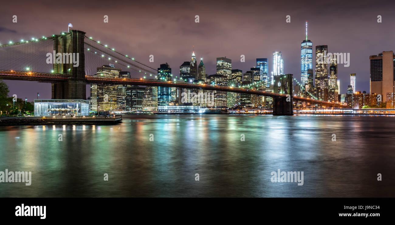 Vista panoramica del Ponte di Brooklyn con il quartiere finanziario di grattacieli al crepuscolo e nuvole di luce. Immagini Stock