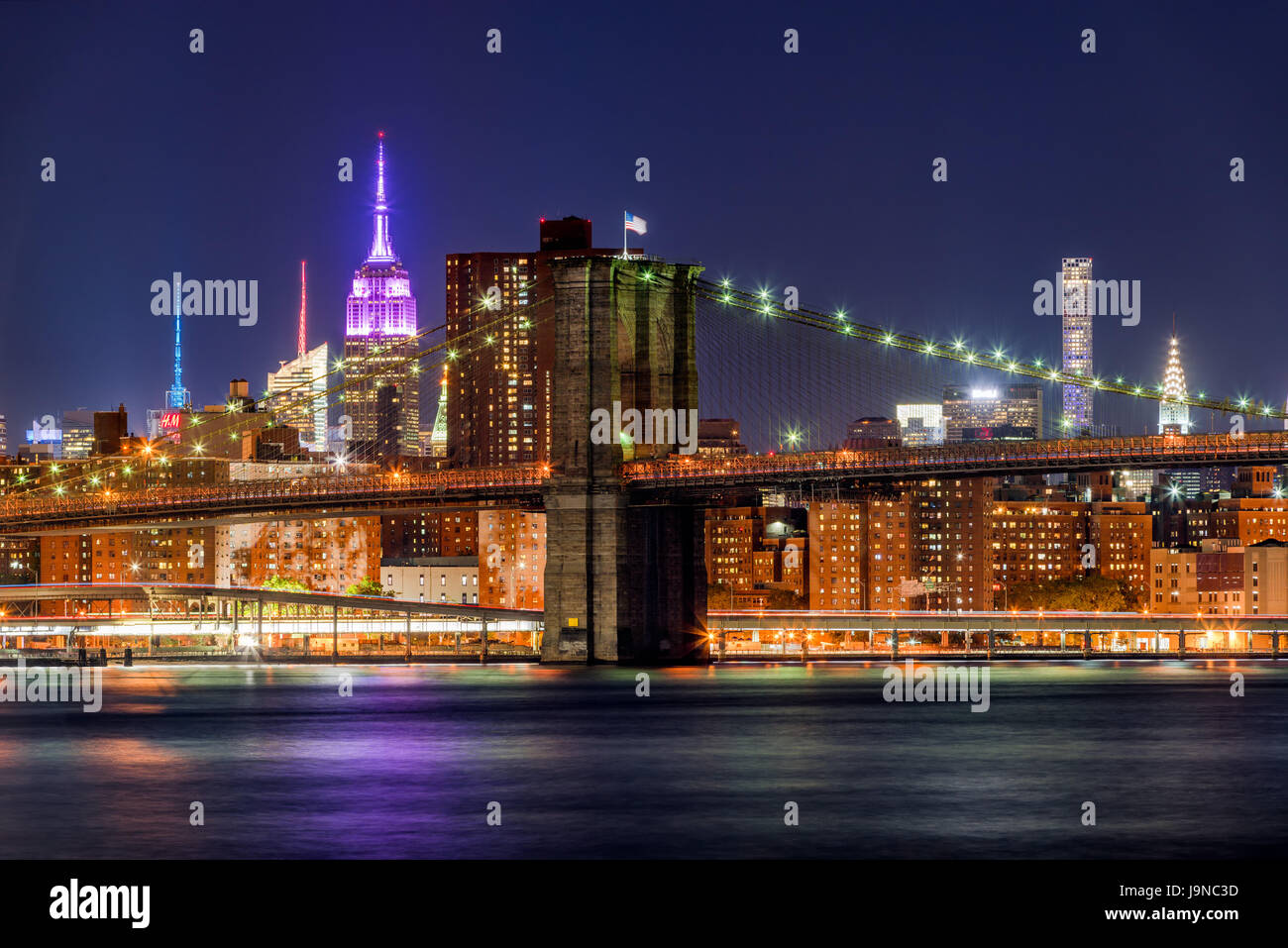 Vista notturna del Ponte di Brooklyn e grattacieli di Manhattan con l' Empire State Building illuminato in rosa. Foto Stock