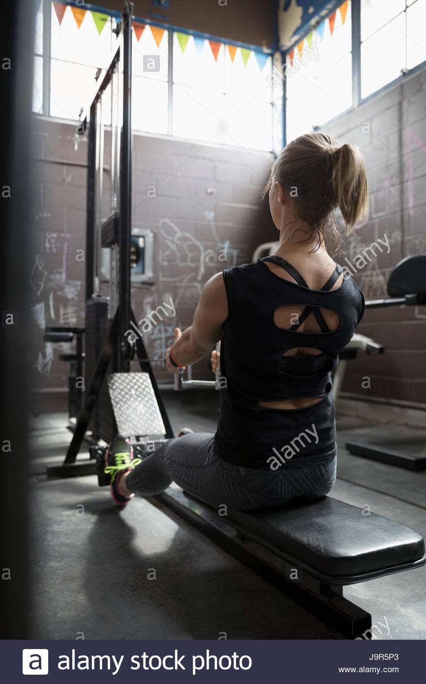 La donna il sollevamento pesi, facendo seduto righe nella palestra grintoso Immagini Stock