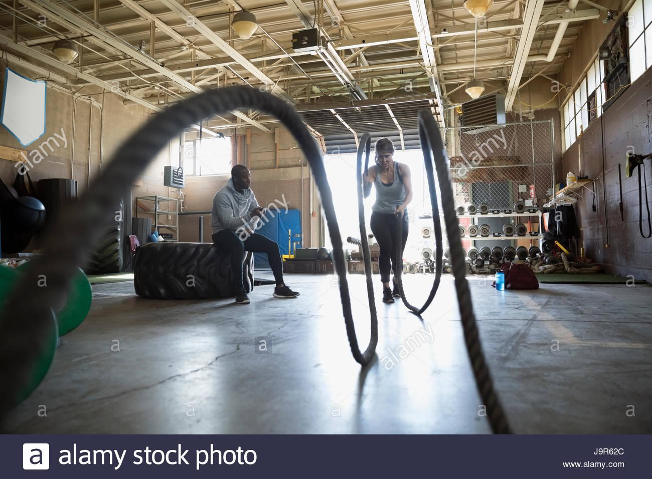 Maschio di personal trainer guardando client femmina facendo crossfit combattendo funi esercizio in palestra Immagini Stock