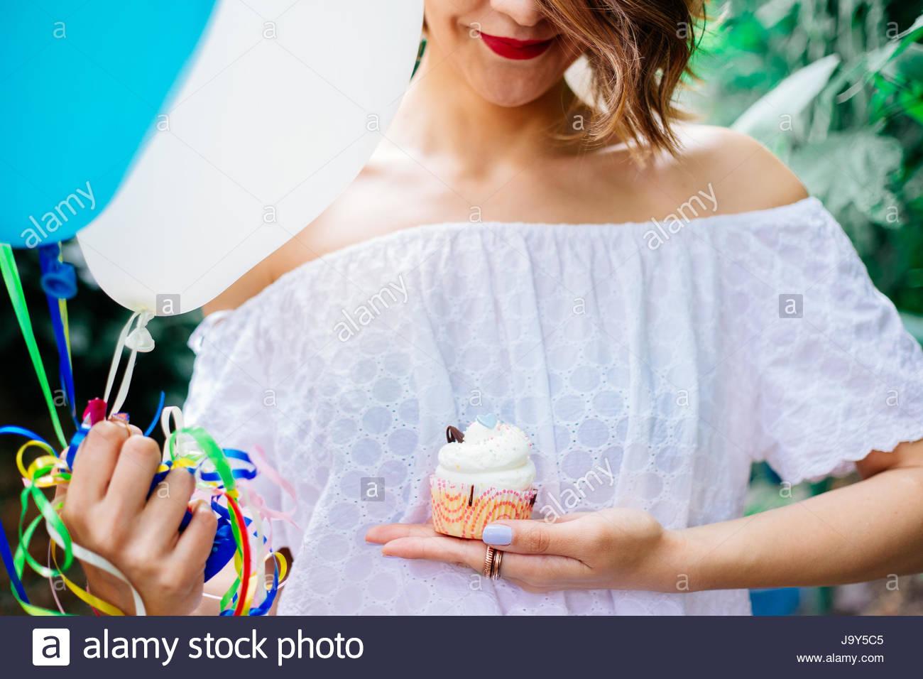 La donna è felice con la sua torta di compleanno Immagini Stock
