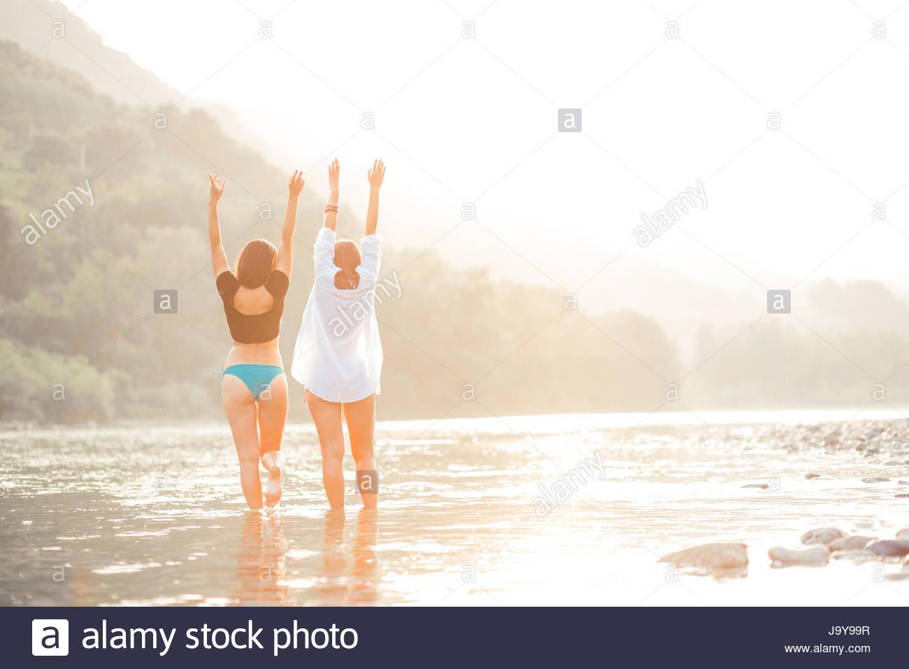 Giovani donne sulla spiaggia di tramonto avente una buona volta Immagini Stock