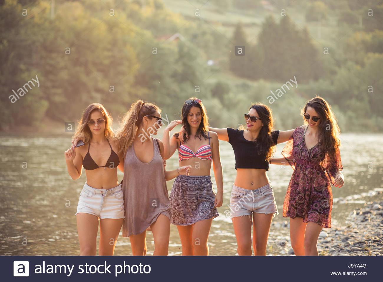 Giovani donne godono sulla spiaggia sul giorno di estate Immagini Stock