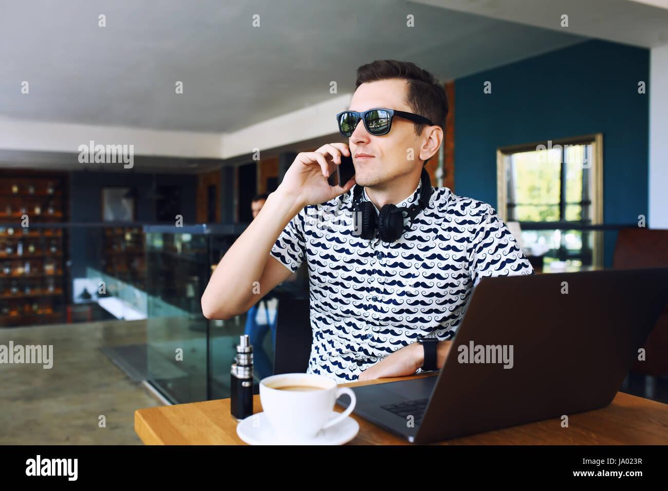 Giovane bello hipster uomo in sunglases seduto in cafe parlando del telefono cellulare. Sul computer portatile sul Immagini Stock