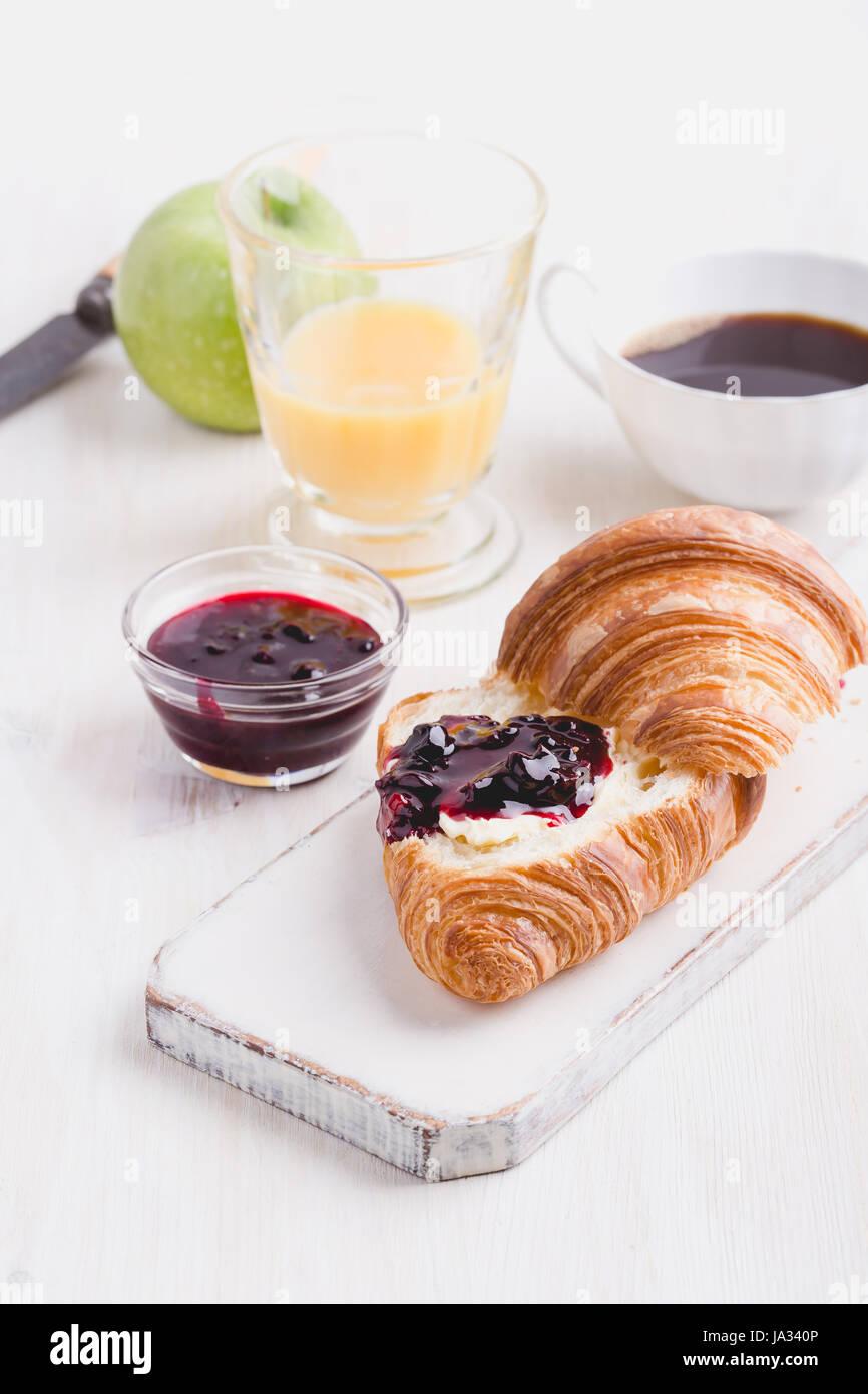 La colazione sul bianco sullo sfondo di legno - croissant, marmellata, succo di frutta e caffè Immagini Stock