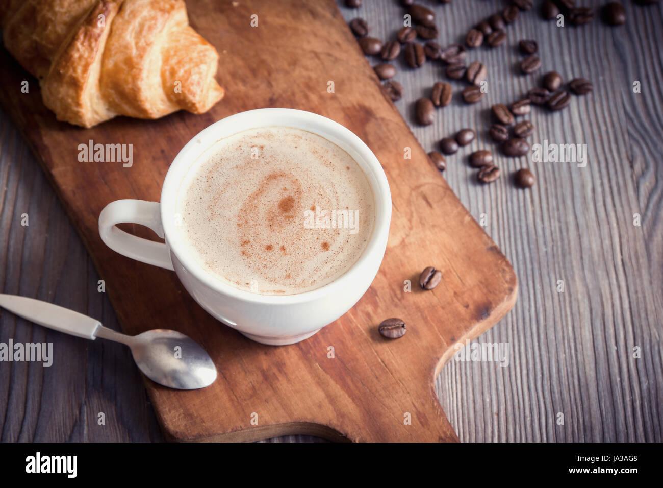 Caffè con croissant per la colazione. Caffè cappuccino, tint immagine con copia spazio. Foto Stock