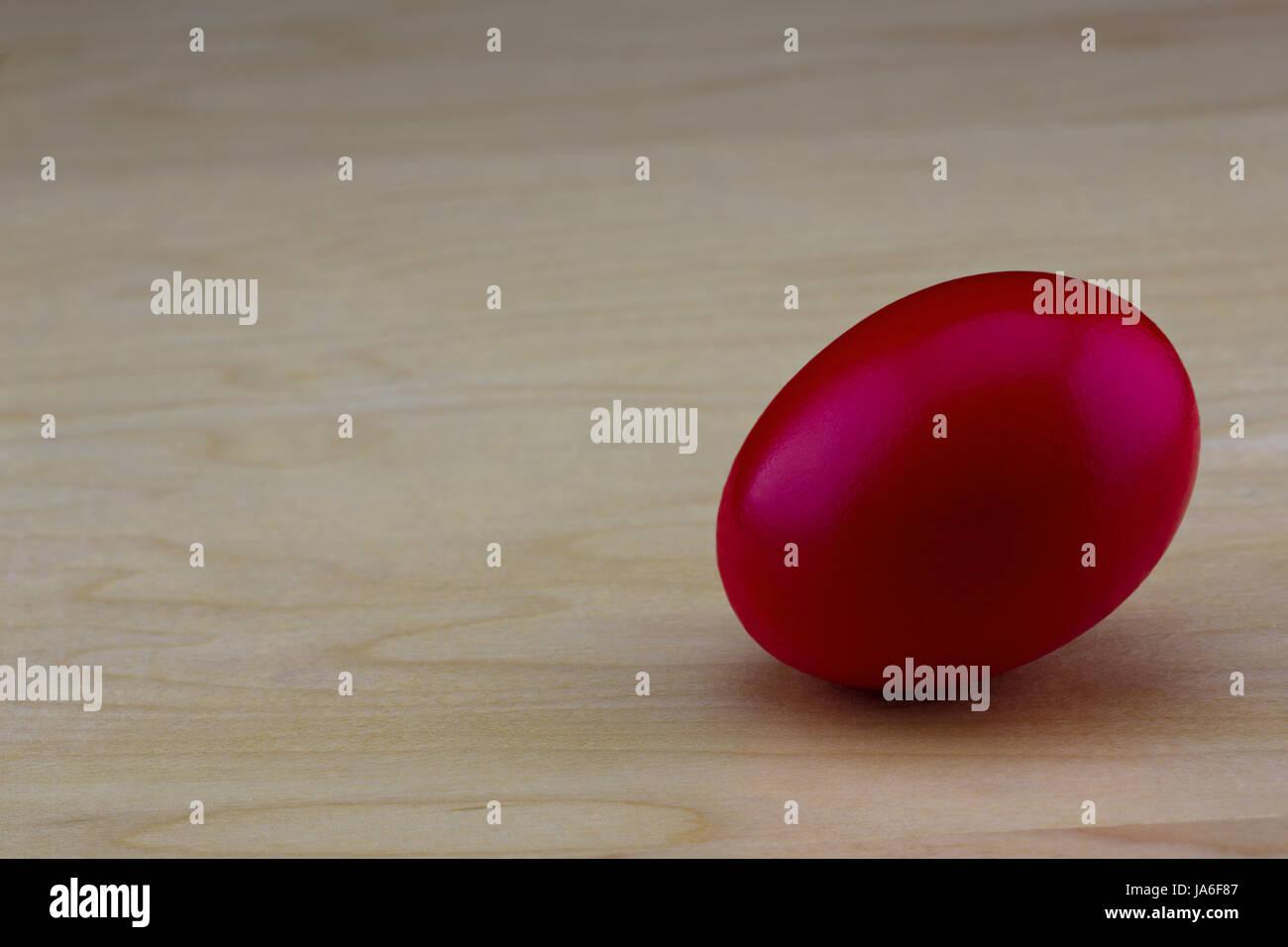 Rischi e sfide per gli investimenti di successo si vede in rosso porpora nido uovo sulla grana di legno con sfondo Immagini Stock