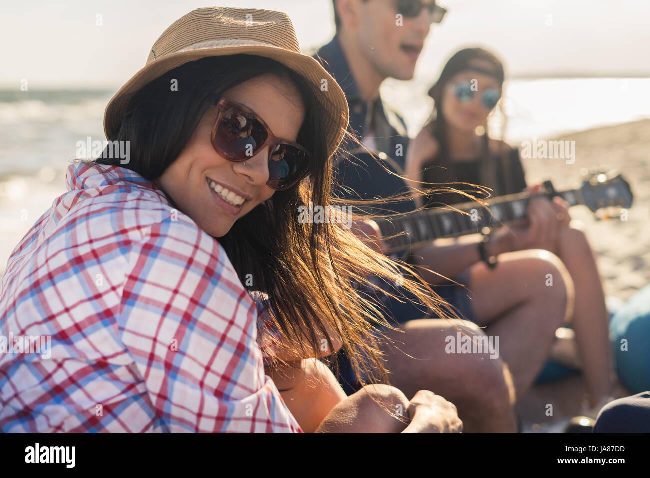 Il gruppo di amici con la chitarra su la festa in spiaggia Immagini Stock