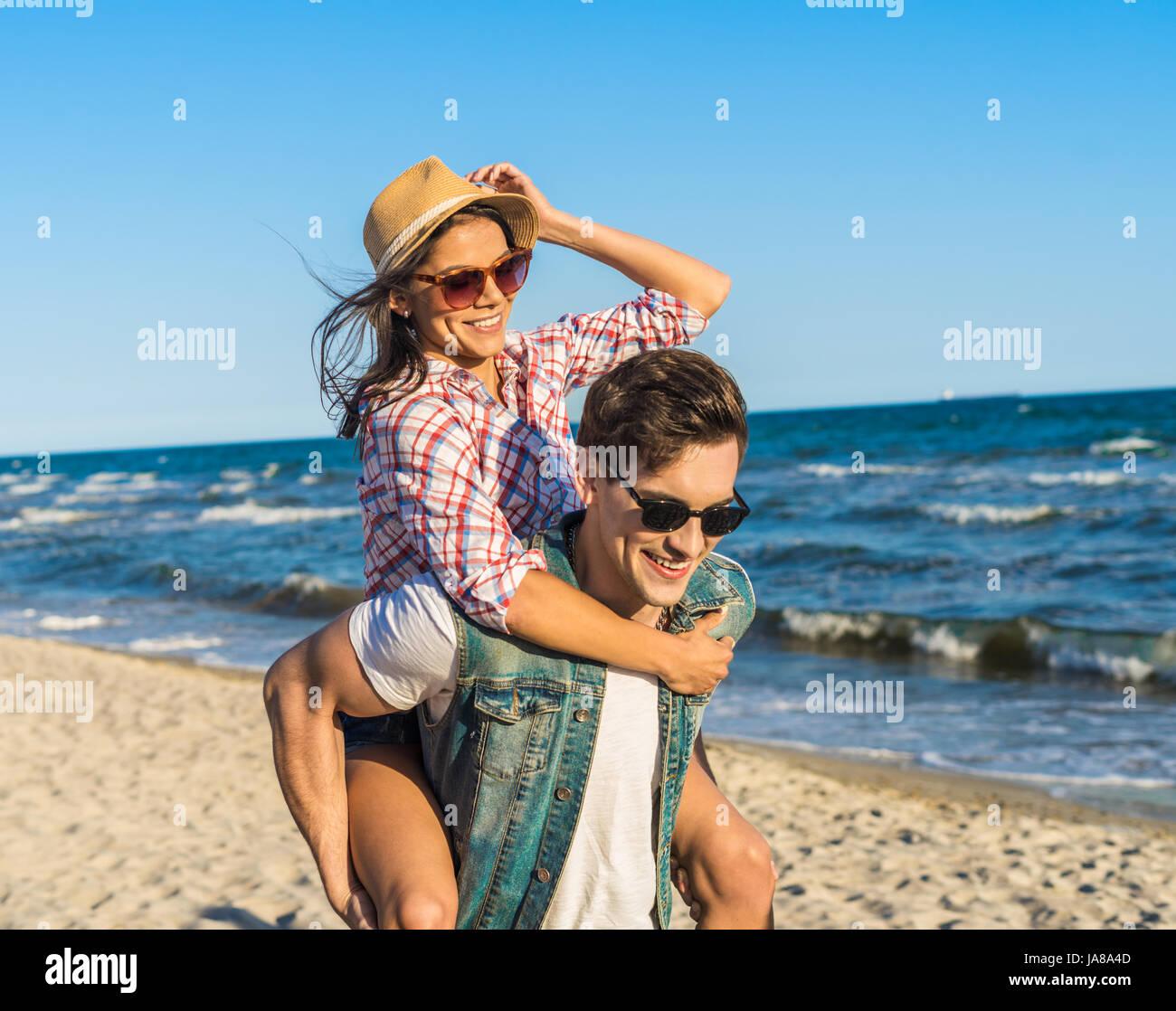 Giovane coppia divertenti in occhiali da sole piggybacking sulla spiaggia. Immagini Stock