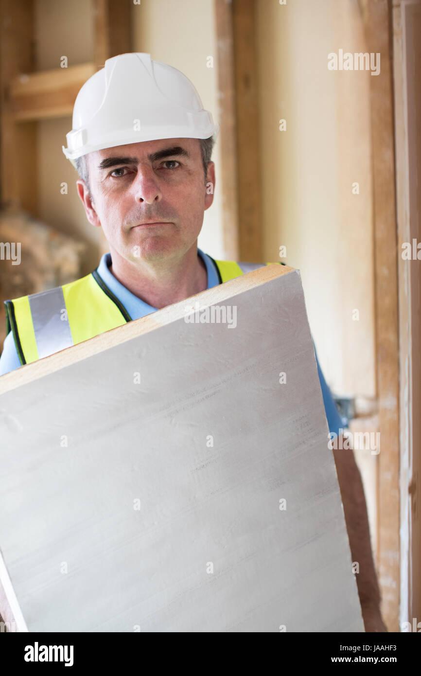 Ritratto di Builder montaggio tavole di isolamento nel tetto della nuova casa Immagini Stock