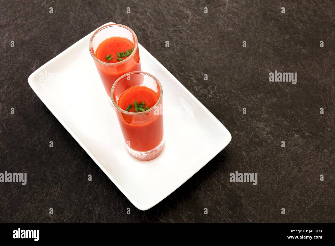 Tapas spagnole in un moderno bar. Due colpi di gazpacho, freddo minestra di pomodoro, al buio su un tavola nera Immagini Stock