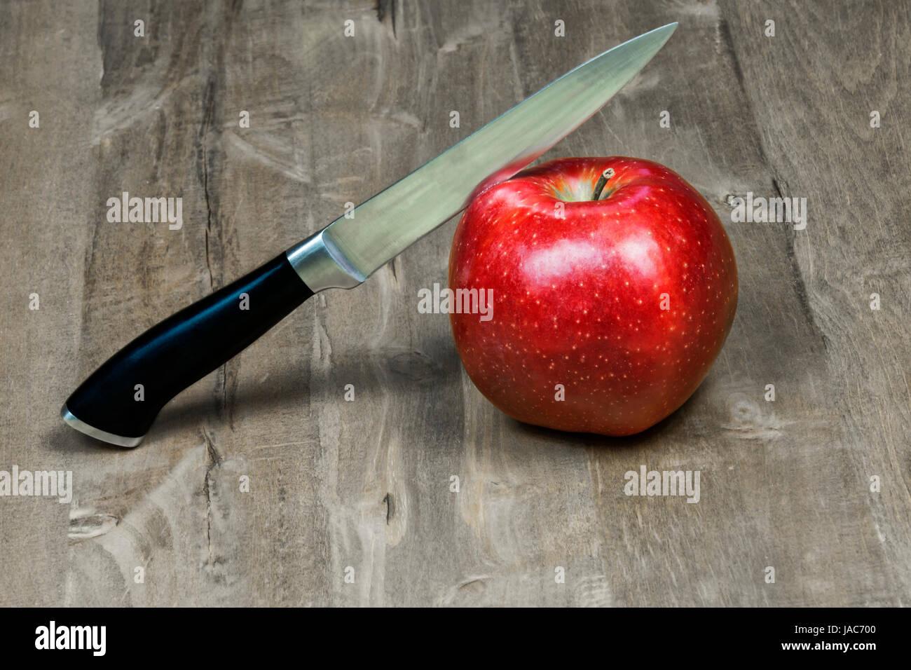 Il coltello taglia una mela rossa giacente su di una superficie di legno Immagini Stock