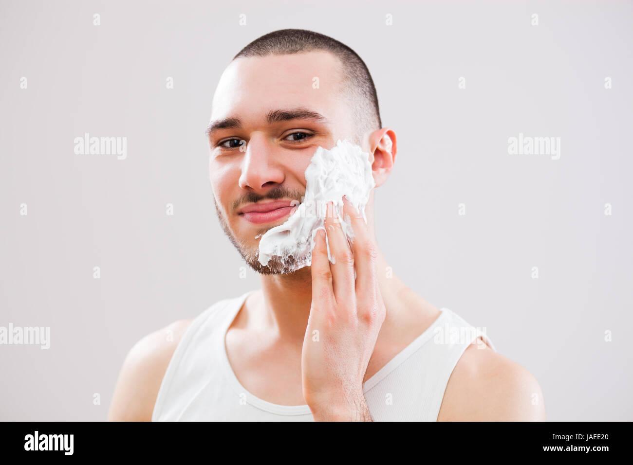 Giovane uomo è l'applicazione di crema di rasatura per il suo volto. Immagini Stock