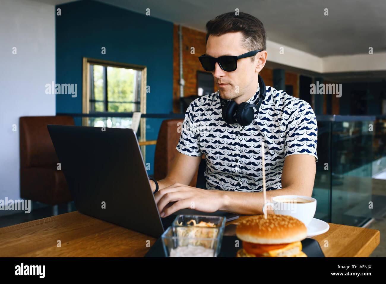Attraente lavoratore di sesso maschile è di usare il computer in caffetteria Immagini Stock