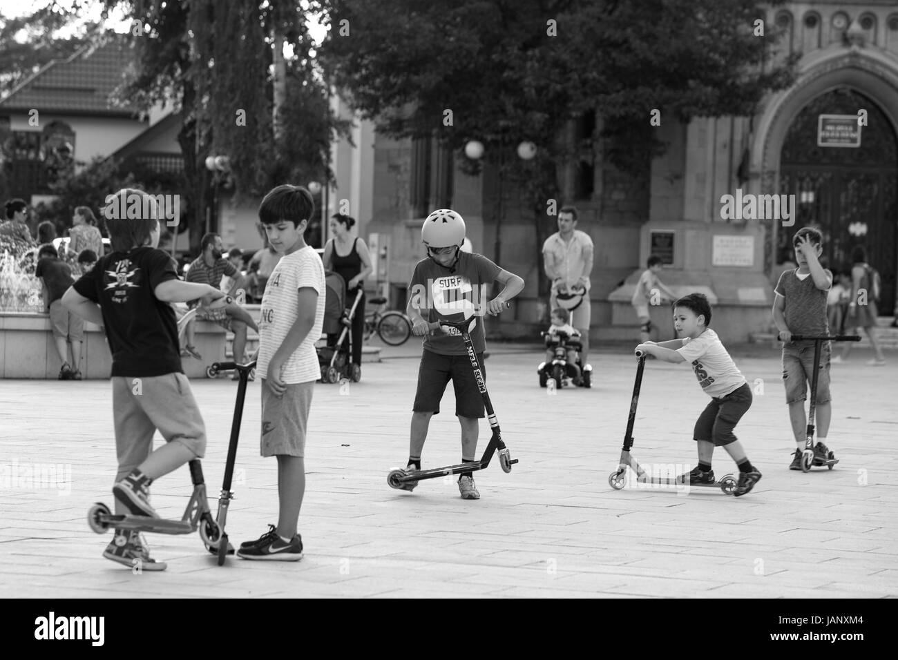 Equitazione per bambini scooter, giocando presso la piazza principale, la vita quotidiana, , kids, strade, centri Immagini Stock