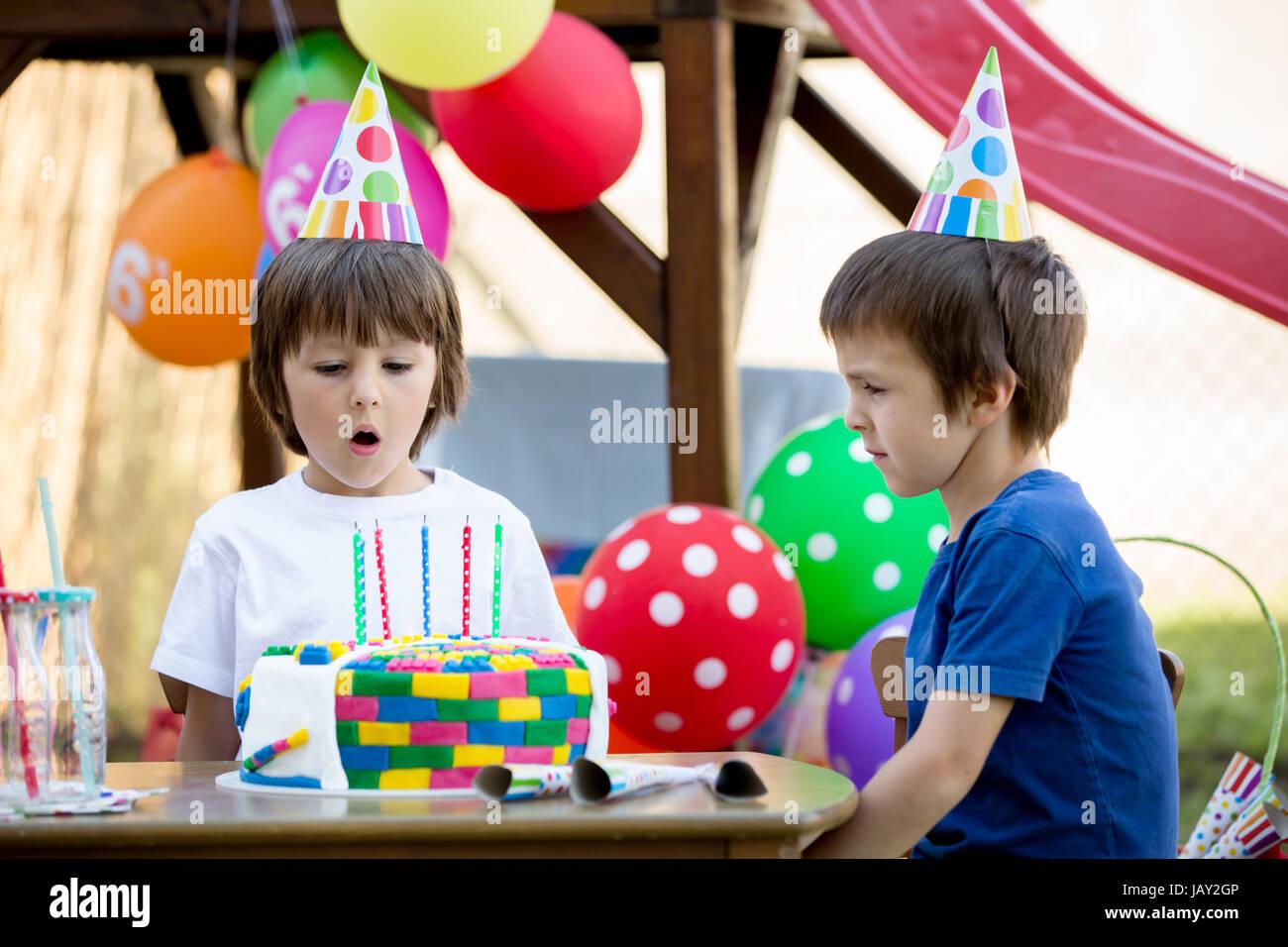 Piccola e dolce bambino, ragazzo, celebra il suo sesto compleanno, torta, palloncini, candele, biscotti. Infanzia Immagini Stock