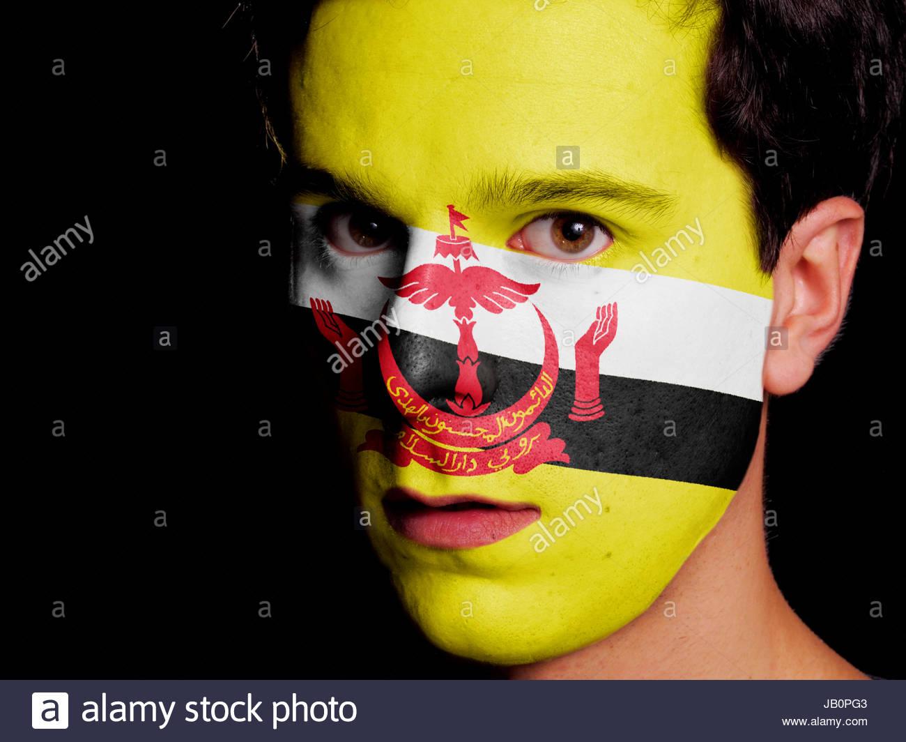 Bandiera del Brunei dipinta su una faccia di un giovane uomo Immagini Stock