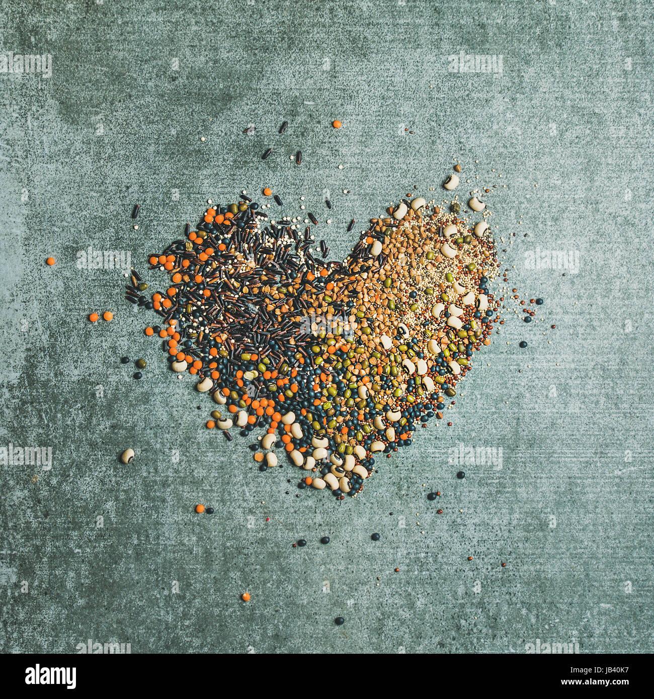 Vari cereali grezzi, fagioli, cereali in forma di cuore Immagini Stock