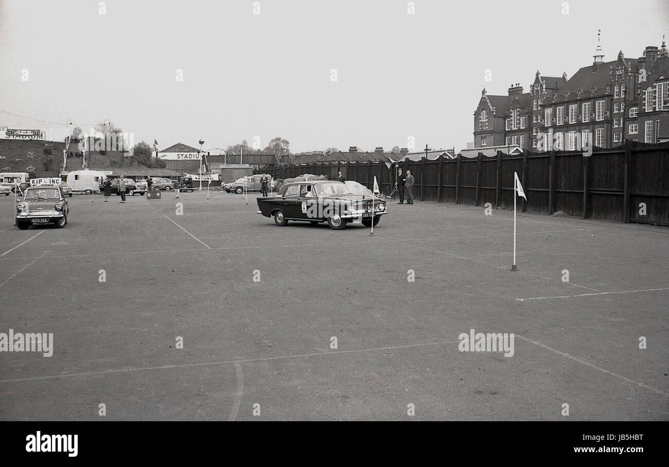 Anni sessanta, storico, immagine mostra auto negoziando attorno flagposts nel parcheggio Catford Greyhound Stadium, Immagini Stock