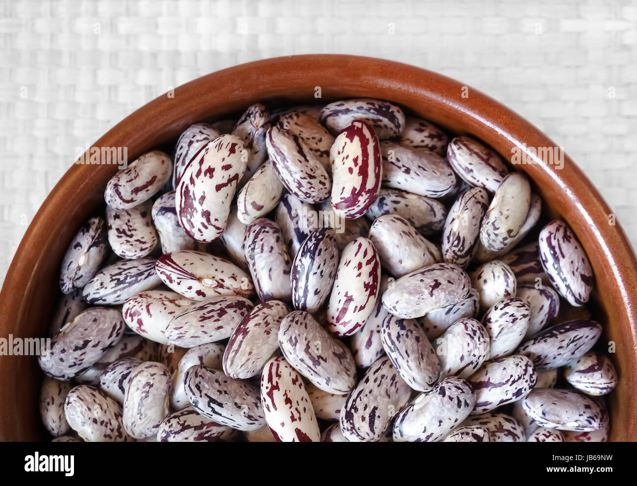 Ciotola piena di chicchi crudi, su sfondo bianco. Vista da sopra. Immagini Stock