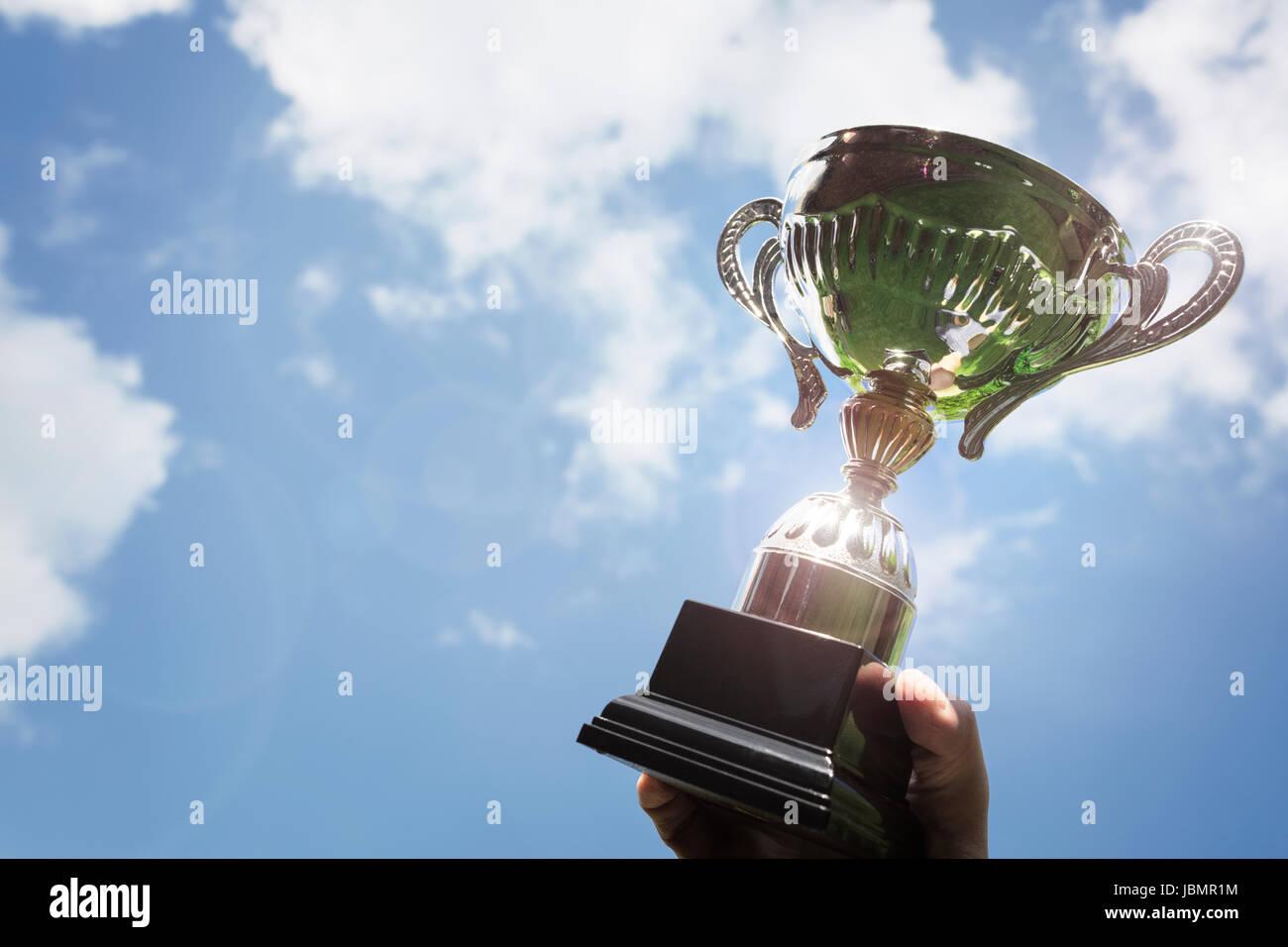 Celebrando con trophy award per il successo o il primo posto del campionato sportivo win Immagini Stock
