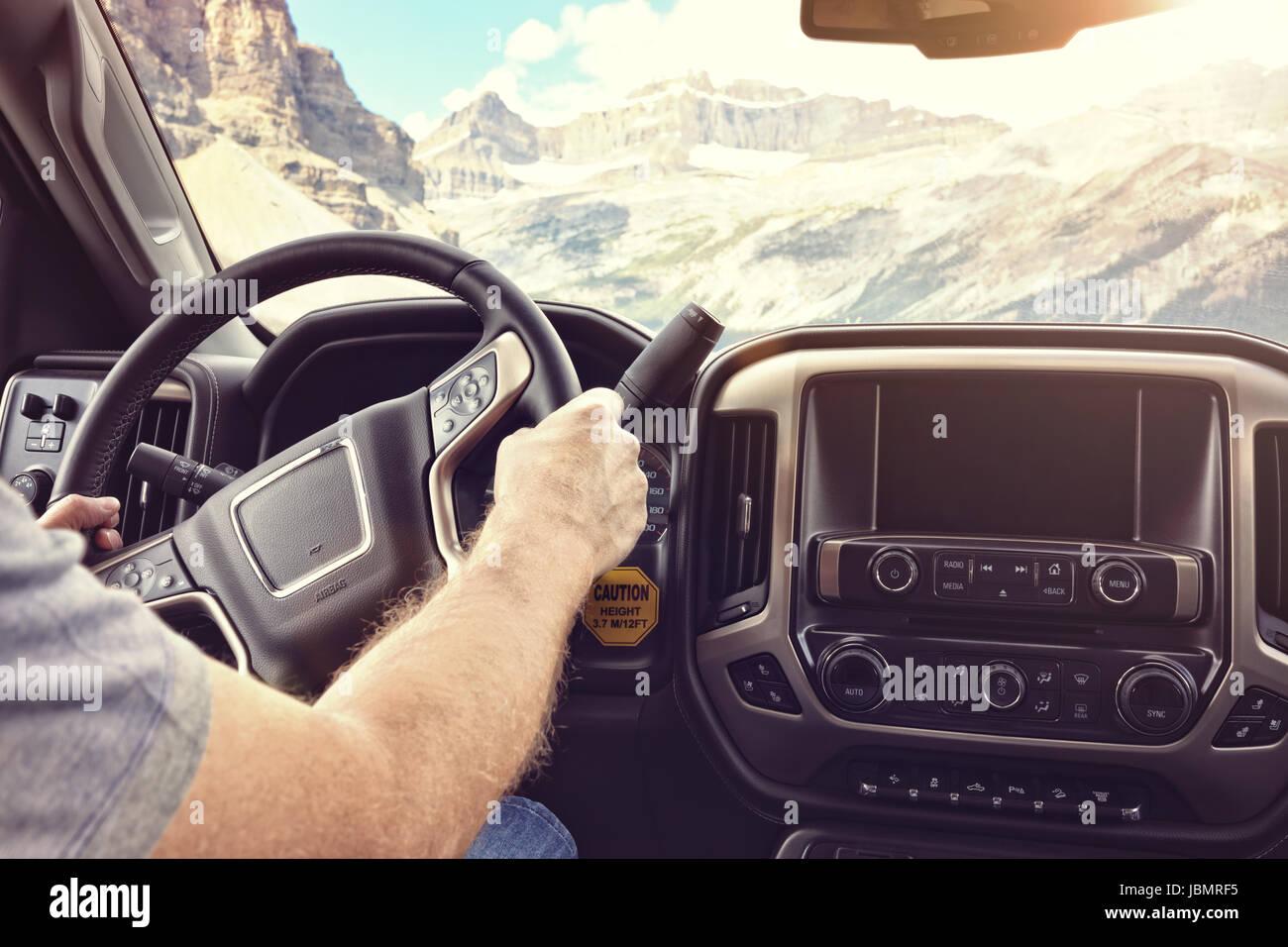 Uomo che tiene il volante di guida di un auto o camion su una strada rurale attraverso le montagne Immagini Stock