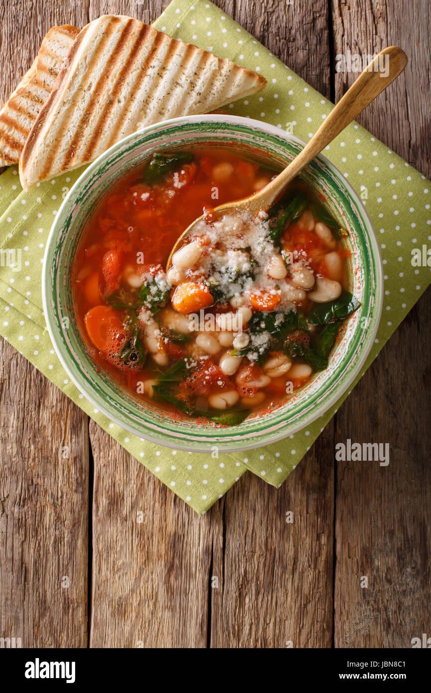 Zuppa di pomodoro con fagioli, spinaci e parmigiano vicino sul tavolo. vista verticale da sopra Immagini Stock