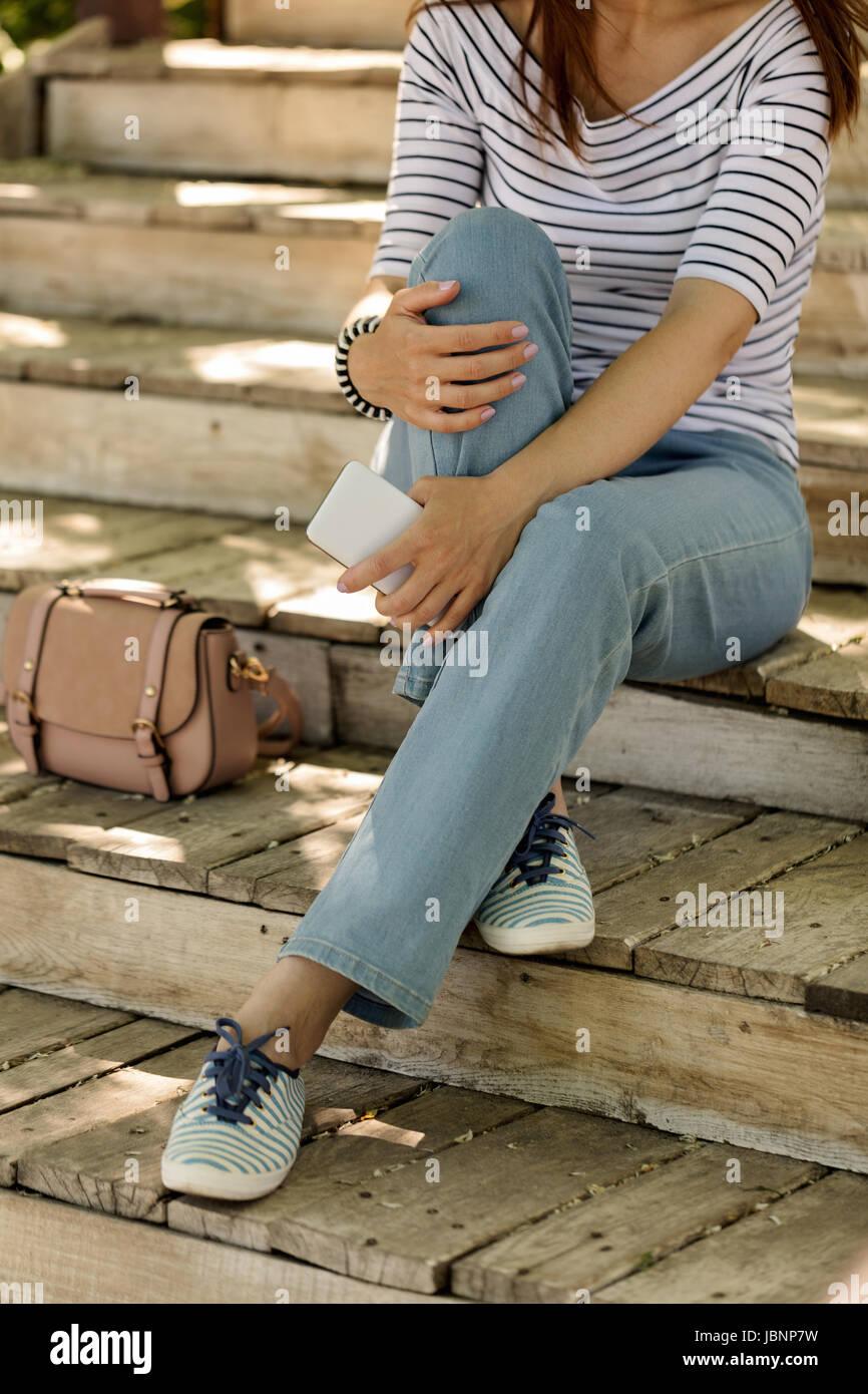 nuovo stile e1a39 8efe5 Giovane donna in blue jeans e scarpe da ginnastica a strisce ...
