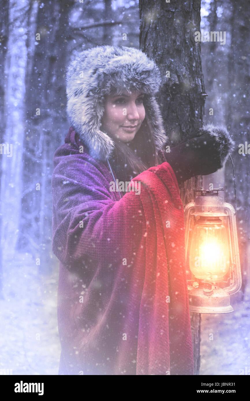 Donna con la lanterna nel bosco invernale Immagini Stock