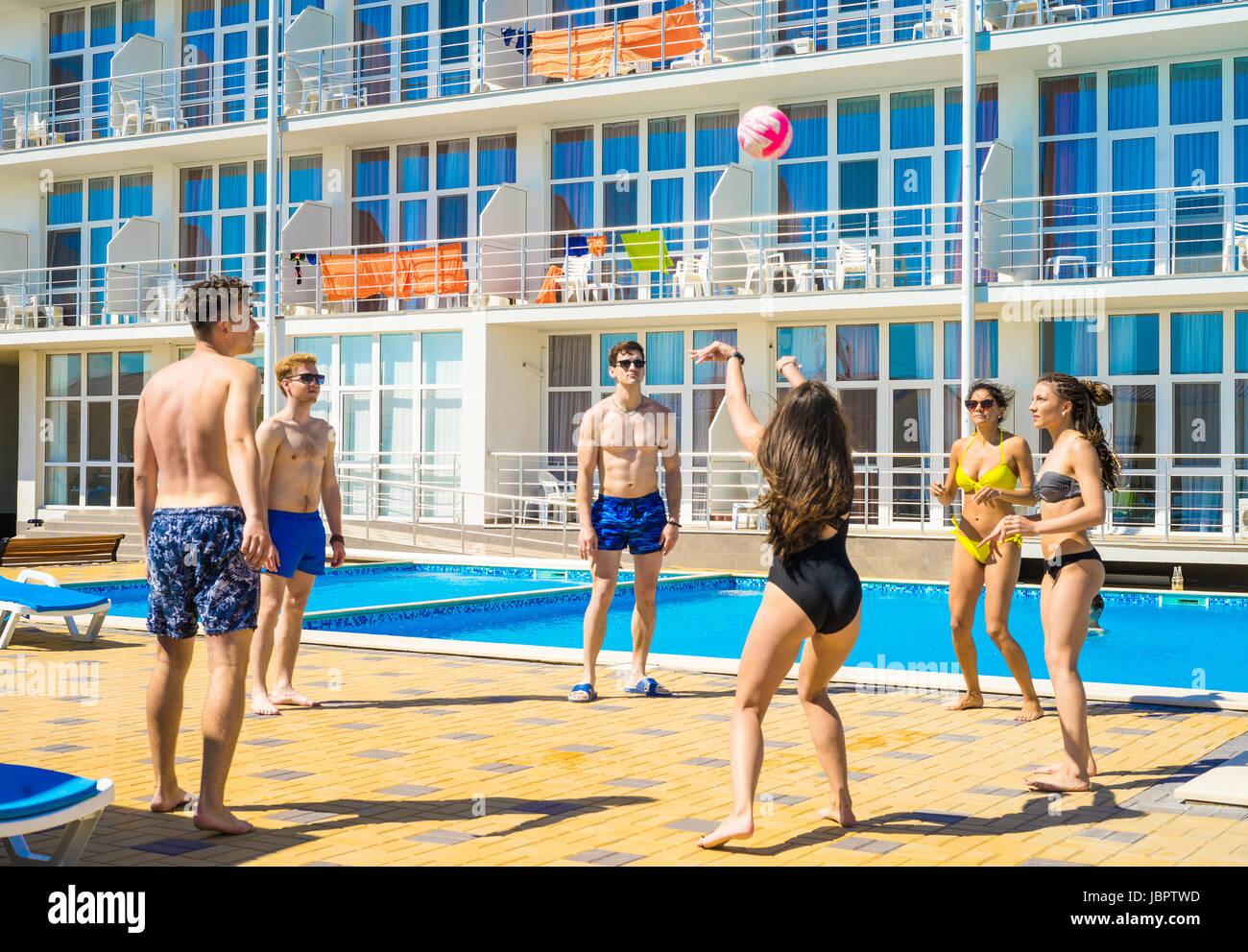 Il gruppo di allegro coppie amici giocando a pallavolo Immagini Stock