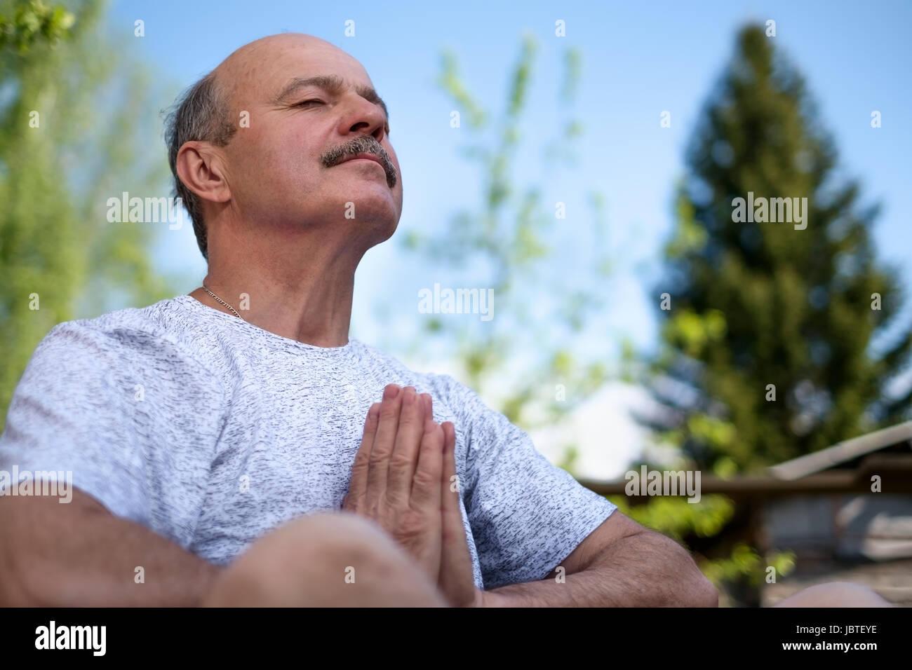 Senior uomo con i baffi con namaste seduta.Concetto di calma e di meditazione. Immagini Stock