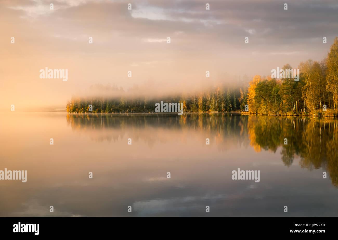 Paesaggio panoramico con il lago e i colori dell'autunno alla luce del mattino Immagini Stock