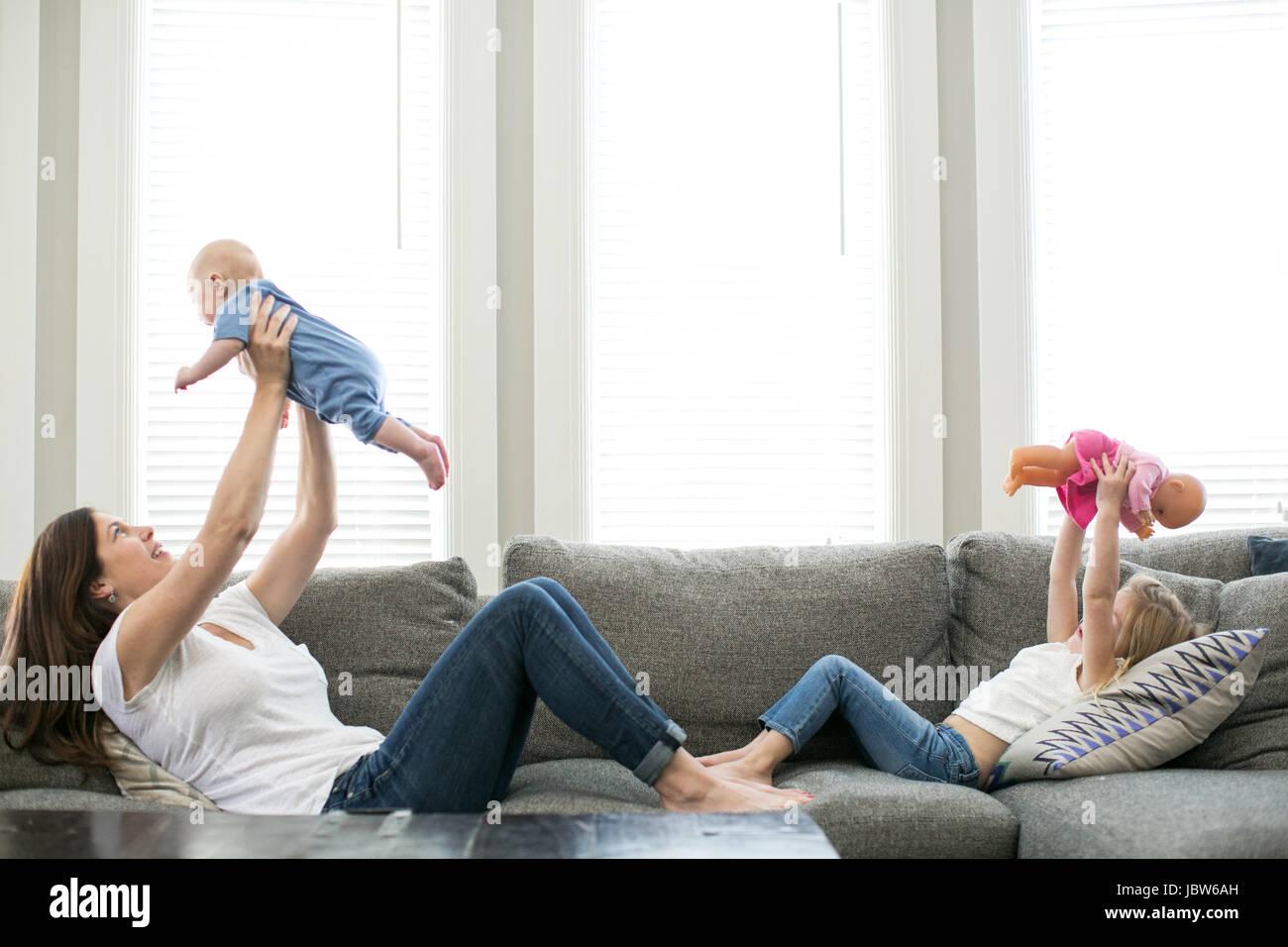 Azienda madre baby boy in aria attraverso dalla figlia tenendo la bambola in aria Immagini Stock