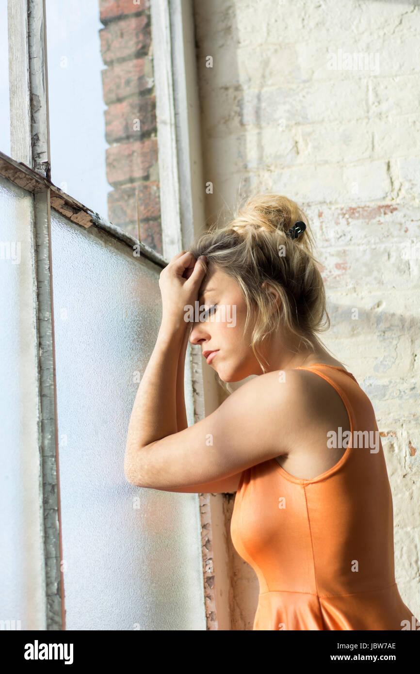 Misere di giovane donna in piedi dalla finestra Immagini Stock