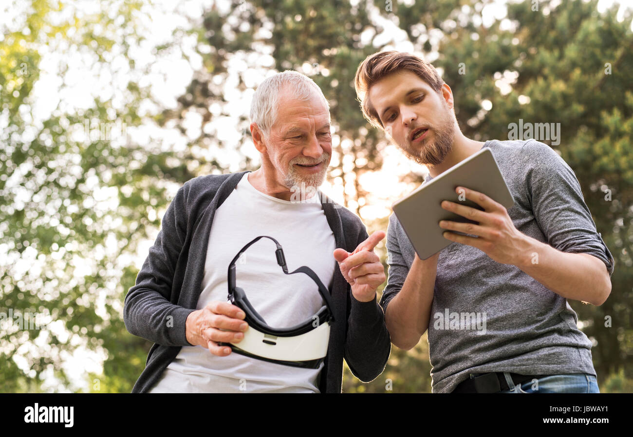 Il giovane e il suo anziano padre con occhiali VR all'esterno. Immagini Stock