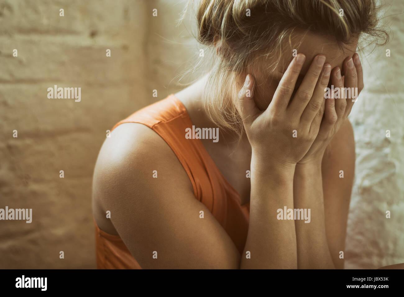 Close up di un triste giovane donna nasconde il viso con le mani il pianto Foto Stock