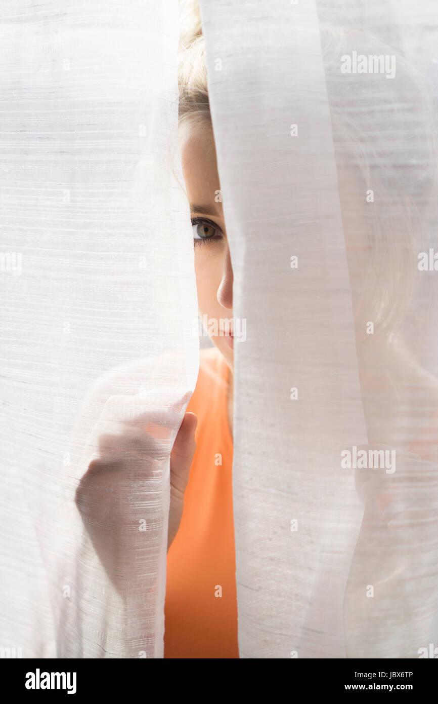 Ritratto di una giovane donna sbirciare dietro le tende Immagini Stock