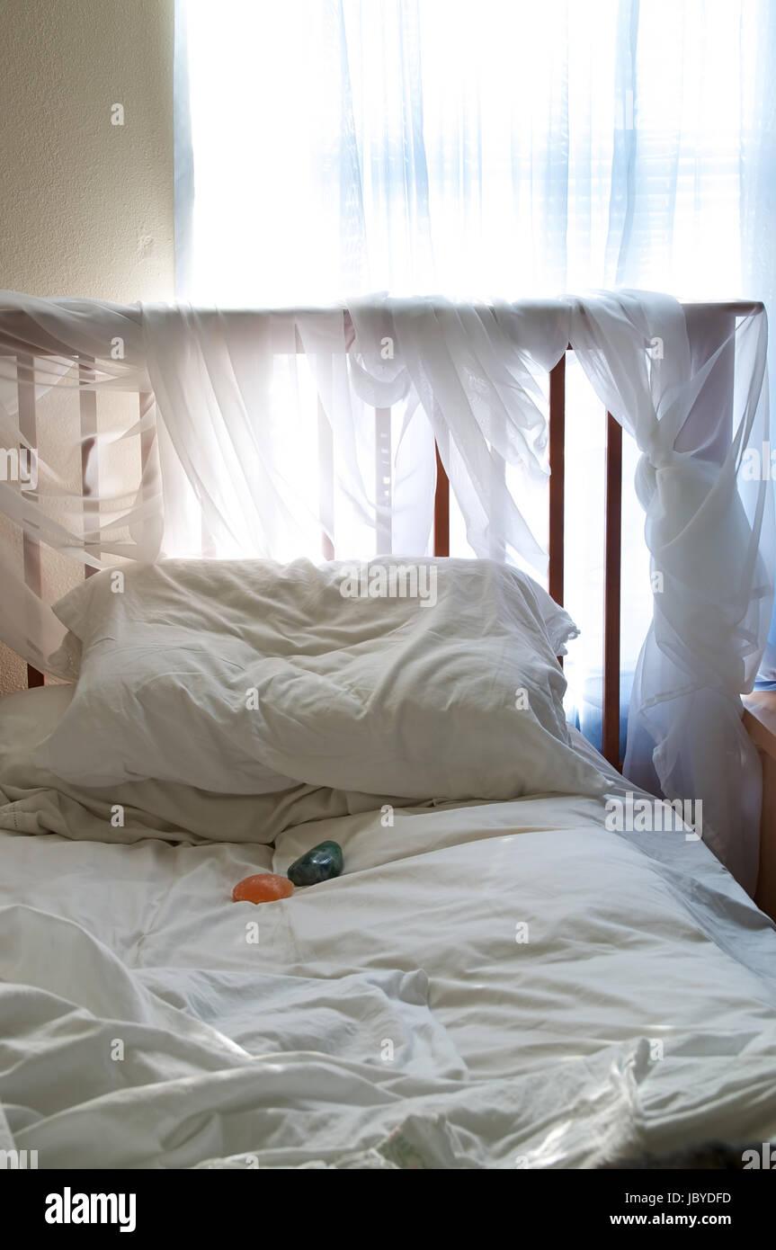 Testate Del Letto In Tessuto.Una Semplice Camera Da Letto Sotto La Luce Ambiente Dalla Finestra