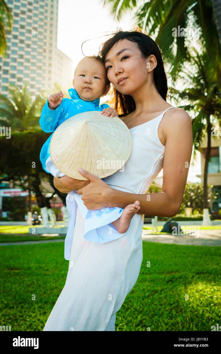Una madre contiene la sua piccola figlia in Vietnam tradizionale clothers aodai nelle sue braccia sulla spiaggia Immagini Stock