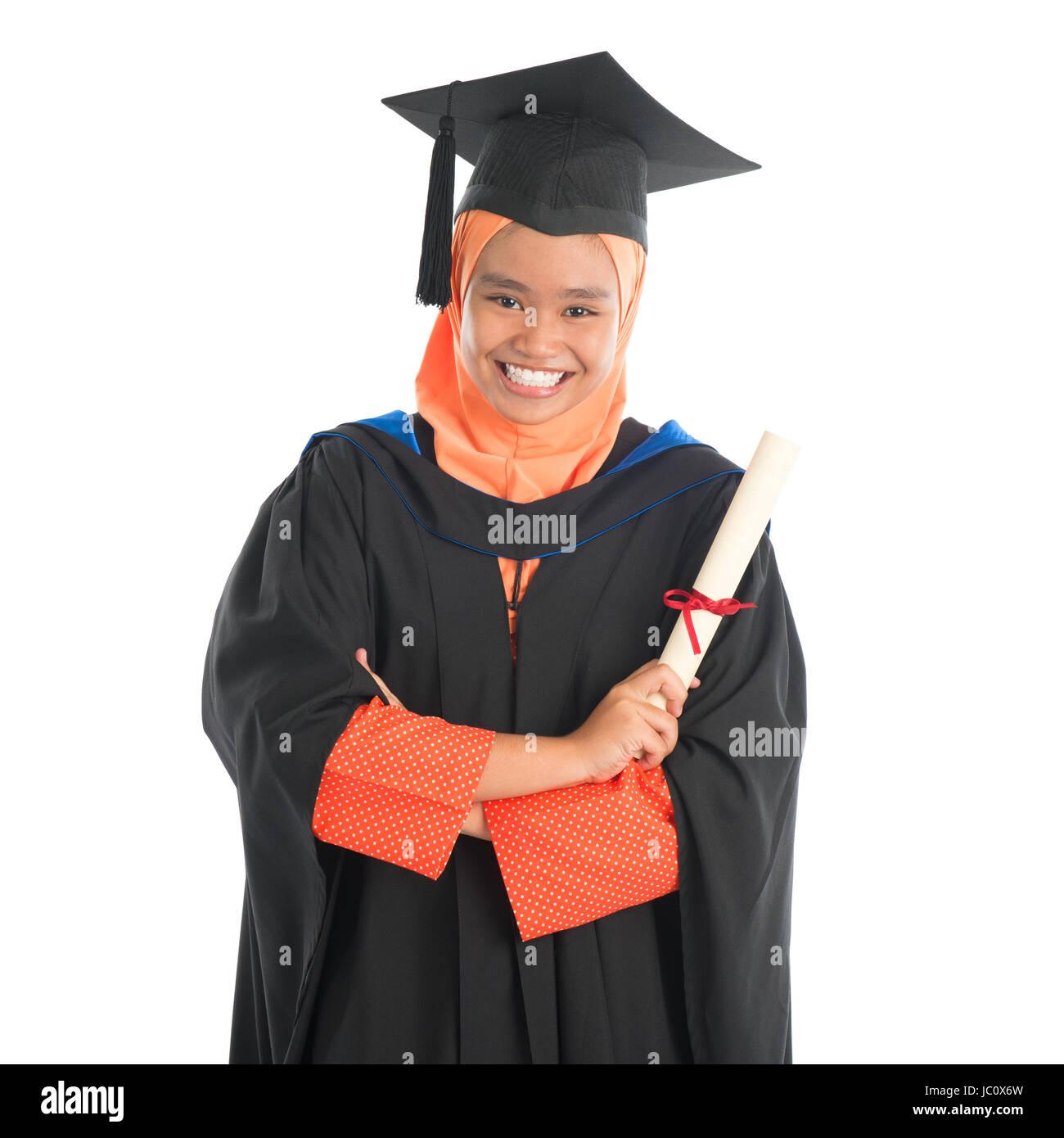 Ritratto di sorridere Asian femmina studente musulmano in abito di laureati  che mostra il diploma di laurea in piedi isolato su sfondo bianco. 8a346cd8c741